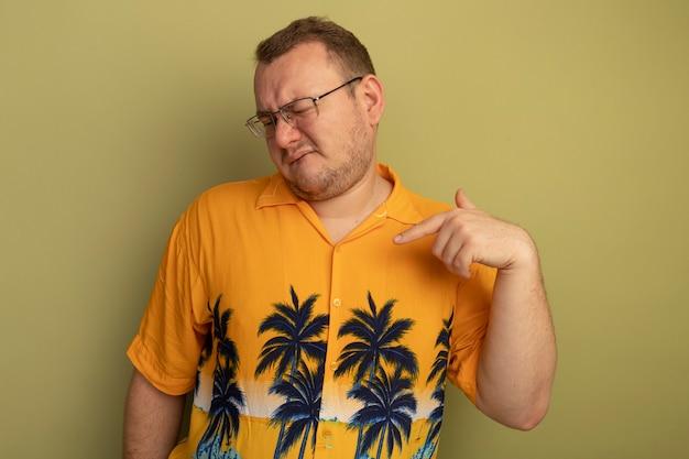 Man in bril met oranje shirt op zoek verward en ontevreden wijzend met vinger naar zichzelf staande over lichte muur