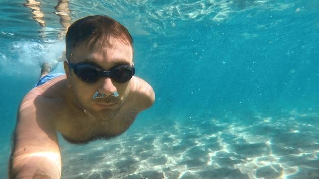 Man in bril zwemmen onder het blauwe en transparante water van de middellandse zee. de camera vasthouden
