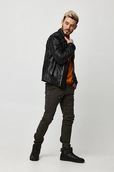 Man in broek en laarzen leren jas oranje trui trend van het seizoen