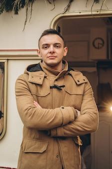 Man in bruin jasje bij de trailer