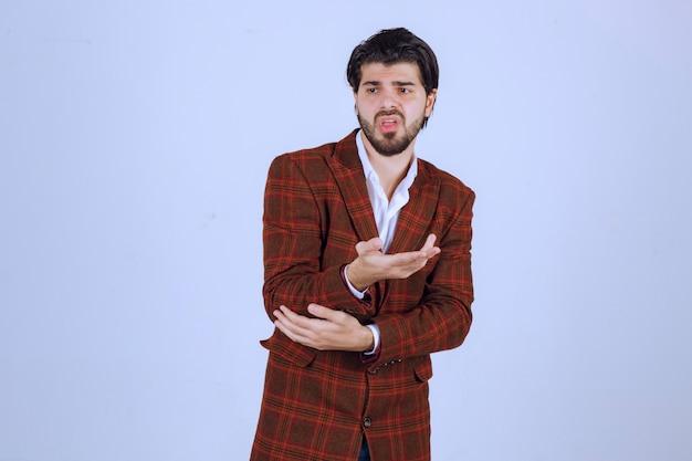 Man in bruin jasje maakte een fout en probeerde zichzelf met open handen uit te leggen.
