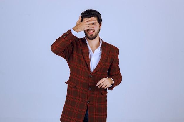 Man in bruin jasje verbergt zijn gezicht met de hand.
