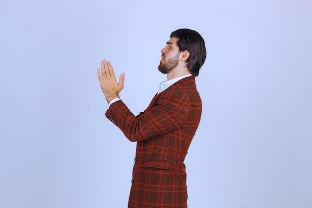 Man in bruine blazer die zijn handen verenigt en bidt.
