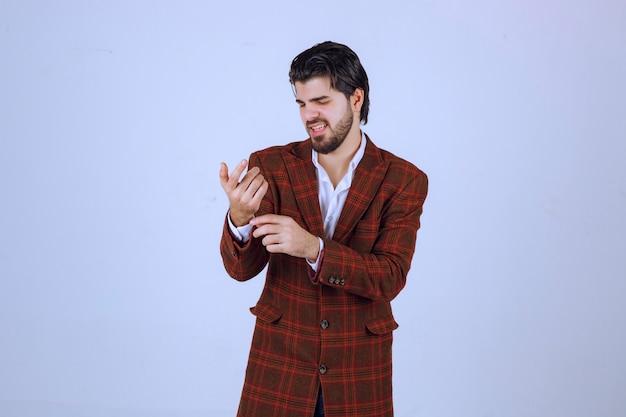 Man in bruine blazer die zijn pols controleert.