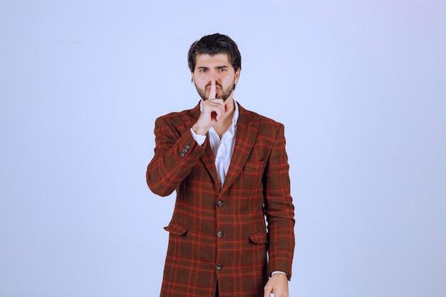 Man in bruine blazer stilte teken maken.