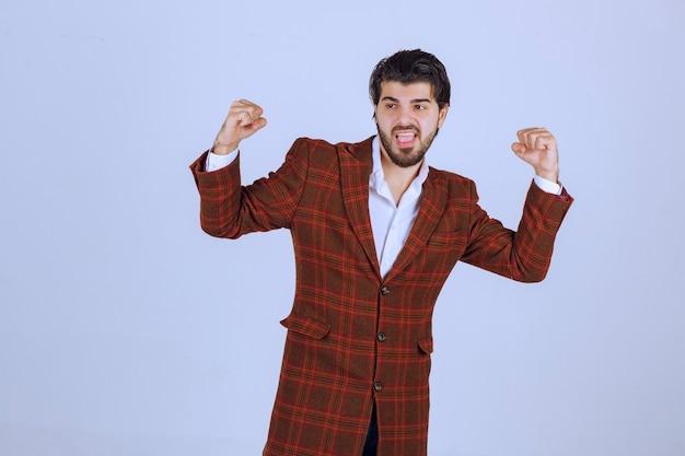 Man in bruine blazer toont zijn vuisten en voelt een hoge motivatie.