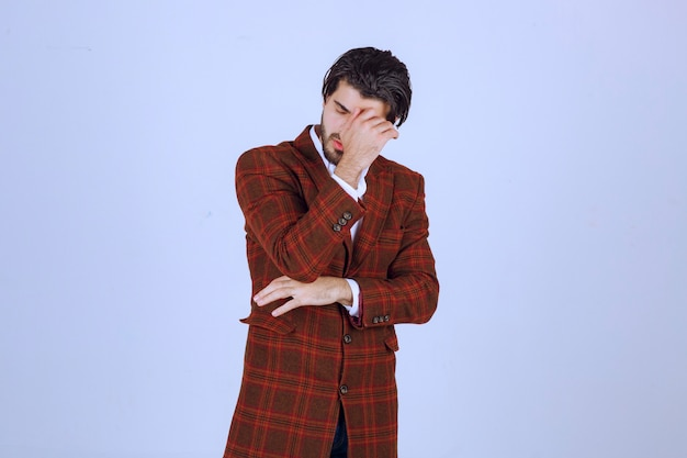 Man in bruine blazer voelt zich ziek of ziek.
