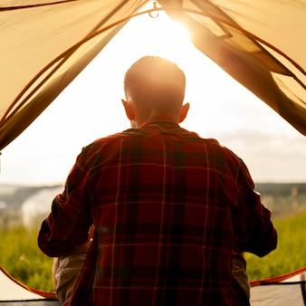 Man in camping tent bij zonsondergang