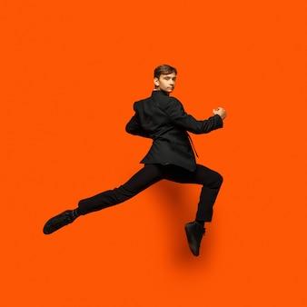 Man in casual kantoor stijl kleren springen geïsoleerd op muur