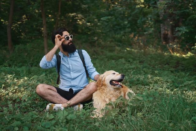 Man in casual kleding en zijn hond kijkt verbaasd naar links
