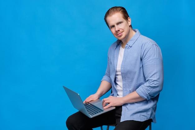 Man in casual kleding op blauw kijkt naar de camersitting met laptop.