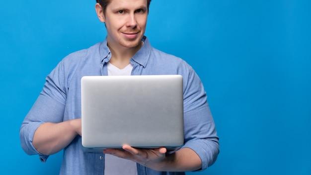 Man in casual kleding op blauw typt op laptop en kijkt naar de camera.