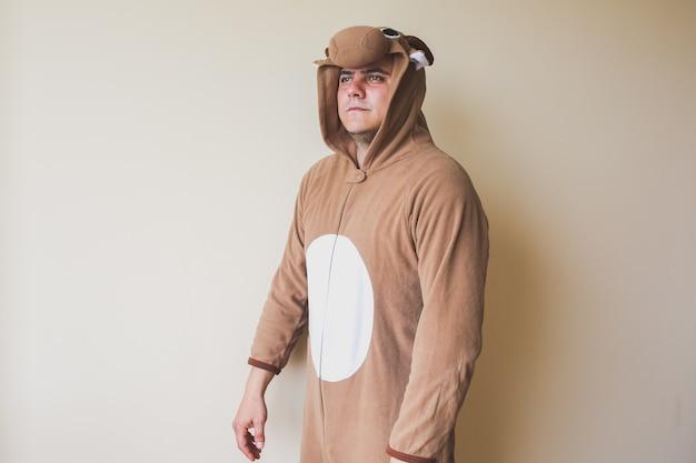 Man in cosplay kostuum in de buurt van de muur. kerel in de grappige nachtkleding van dierenpyjama's.