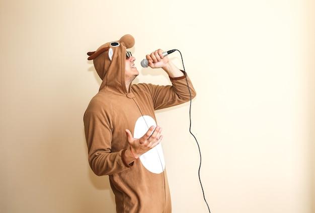 Man in cosplay kostuum van een koe die karaoke zingt. kerel in de grappige dierenpyjama's nachtkleding met microfoon. grappige foto met haspelbandrecorder. feest ideeën. disco-retromuziek.