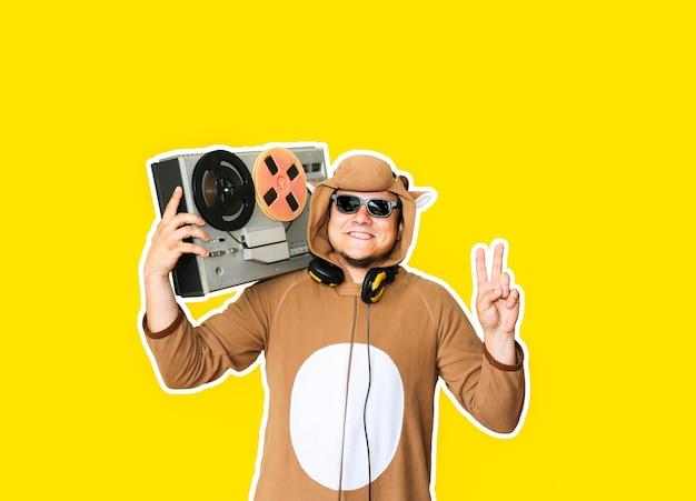 Man in cosplay kostuum van een koe met reel tape recorder geïsoleerd op gele achtergrond. kerel in de nachtkleding van de dierenpyjama. grappige foto met feestideeën. disco-retromuziek.