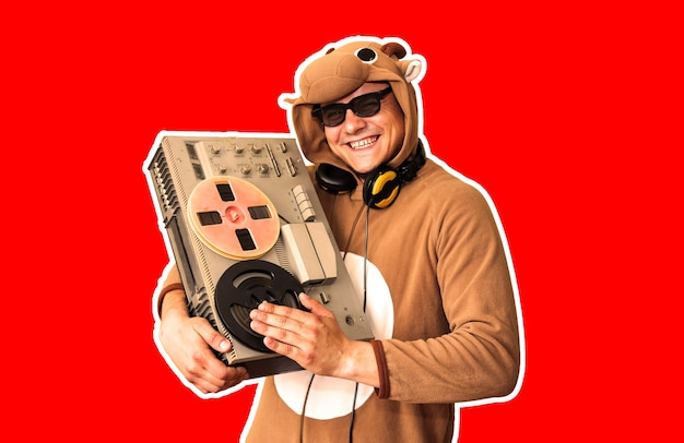 Man in cosplay kostuum van een koe met reel tape recorder geïsoleerd op rode achtergrond. kerel in de nachtkleding van de dierenpyjama. grappige foto met feestideeën. disco-retromuziek.