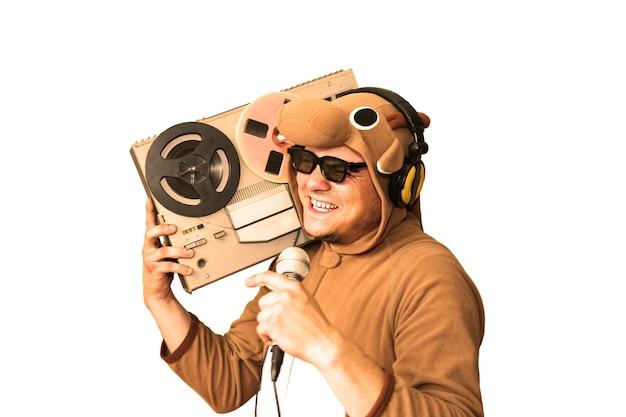 Man in cosplay kostuum van een koe zingen karaoke geïsoleerd op een witte achtergrond. kerel in de dierenpyjama die microfoon vasthoudt. grappige foto met haspelbandrecorder. feest ideeën. disco-retromuziek.