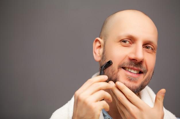Man in de badkamer scheert zijn baard met een scheermes