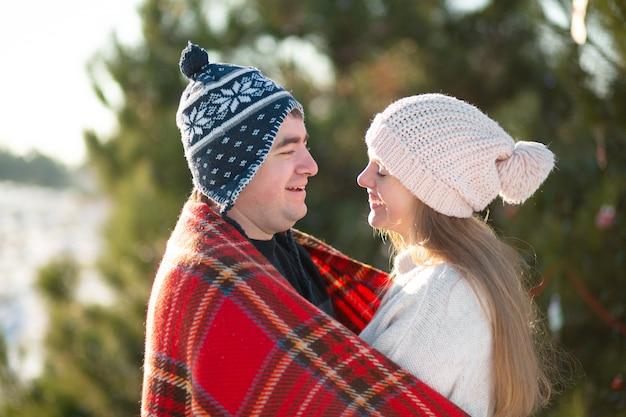 Man in de rode geruite deken wikkelt het meisje zodat ze warm wordt