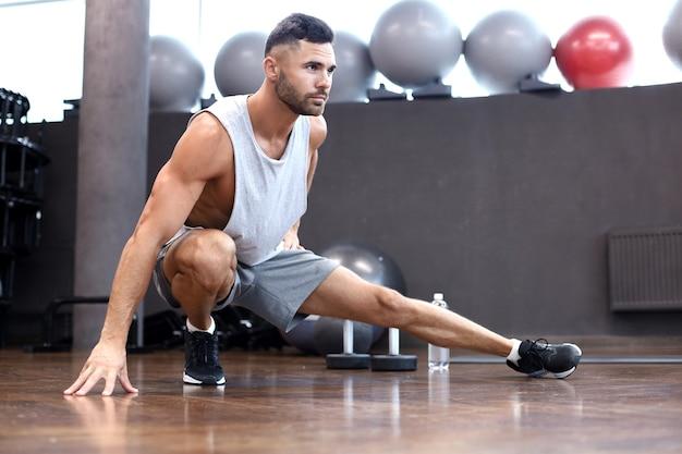 Man in de sportschool doet rekoefeningen op de vloer.