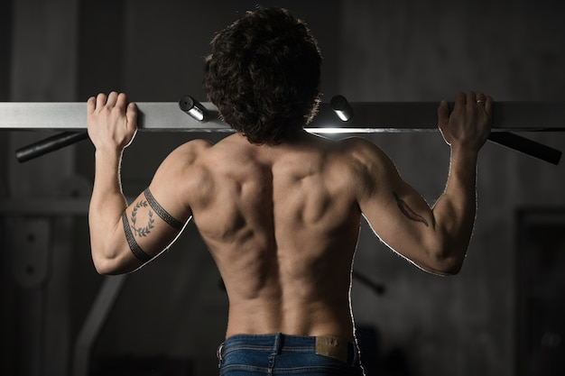 Man in de sportschool maken pull-up. bodybuilder training in de sportschool