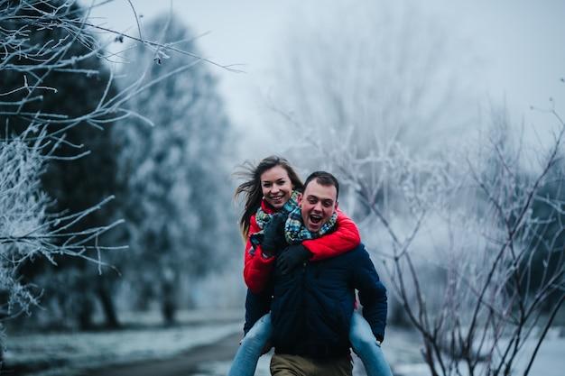 Man in de winter kleding met zijn vriendin in de rug