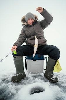 Man in de winterkleren die alleen buiten vissen