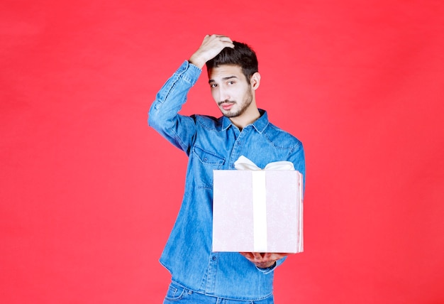 Man in denim overhemd met een paarse geschenkdoos vastgebonden met wit lint en ziet er verward en attent uit.