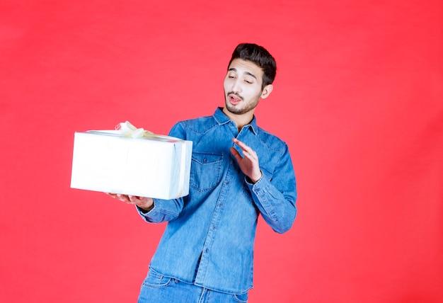 Man in denim shirt met zilveren geschenkdoos en weigering geven.