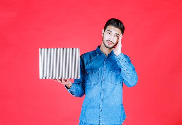 Man in denim shirt met zilveren geschenkdoos en ziet er verward en onverwacht uit.