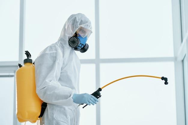 Man in een bacteriologisch beschermingspak dat op kantoor staat