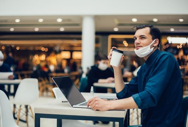 Man in een beschermend masker zittend aan een tafel in een café.