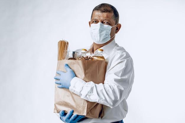 Man in een beschermend medisch masker met een tas uit een supermarkt. voedsellevering