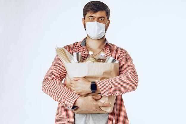 Man in een beschermend medisch masker met een tas uit een supermarkt