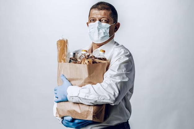 Man in een beschermende medische masker met een zak van een supermarkt
