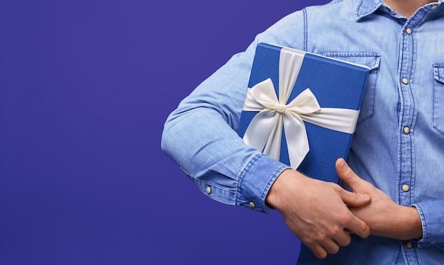 Man in een blauw denim shirt met blauwe geschenk met blauwe pet in zijn hand