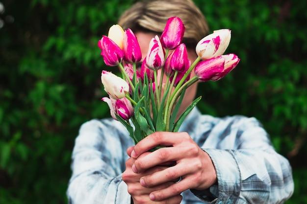 Man in een blauw geruit overhemd heeft een boeket roze tulpen die ze voor zich houden
