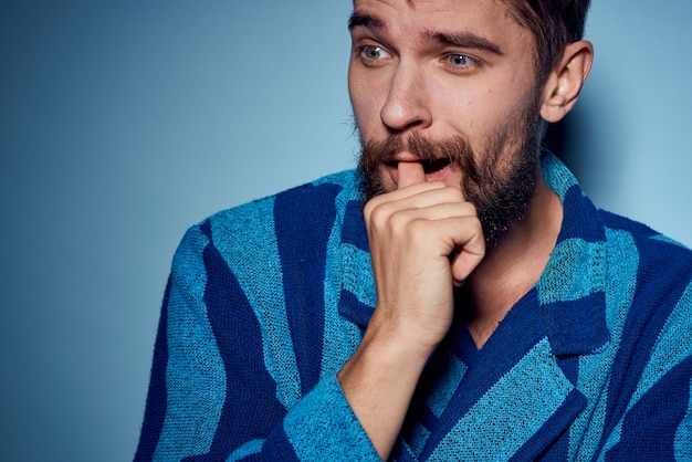 Man in een blauw gewaad met zijn handen naar zijn mond
