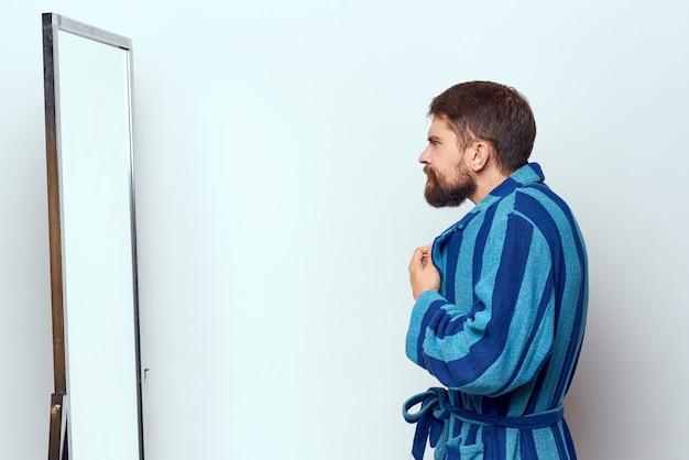 Man in een blauw gewaad onderzoekt zichzelf in een spiegel in een bijgesneden lichte kamer.