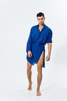 Man in een blauwe jurk op een lichte muur homo model bodybuilder fitness