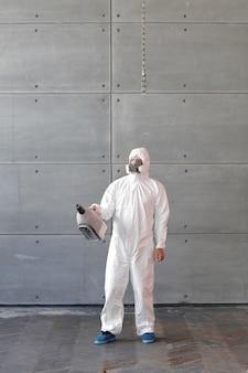 Man in een chemisch beschermingspak en een gasmasker. de man houdt een spuitpistool vast. speciale ontsmetting