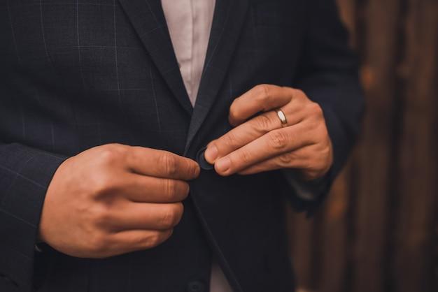 Man in een donker pak die een knop op zijn jas dichtknoopt