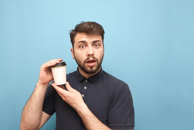 Man in een donker shirt en baard, met een papieren kopje koffie in zijn handen op blauw met een emotioneel gezicht