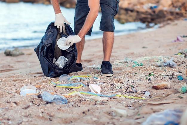 Man in een donker shirt en korte broek met witte handschoenen en een groot zwart pakket dat afval op het strand verzamelt. milieubescherming en planeetverontreiniging concept