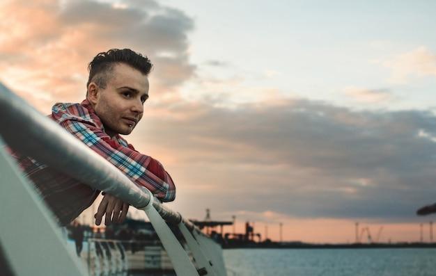 Man in een geruit hemd poseren tegen de achtergrond van de zee, je kunt een deel van het gezicht van dichtbij zien