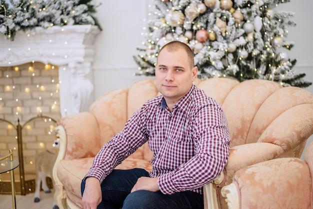 Man in een geruit overhemd zit op een moderne bank in een kerstdecor