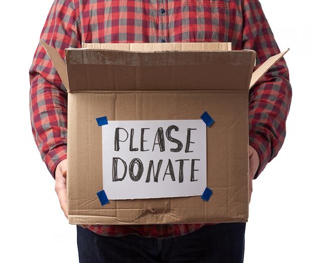 Man in een geruite overhemd en spijkerbroek houdt een bruine kartonnen doos met de inscriptie doneer alstublieft