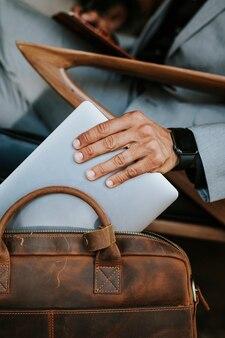Man in een grijs pak die zijn laptop uit een bruine leren tas pakt