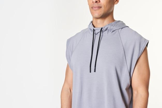 Man in een grijze mouwloze hoodie