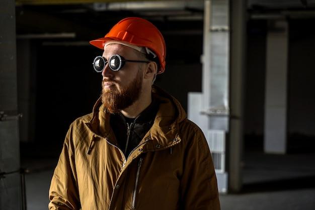 Man in een helm en zonnebril in een donkere kamer, kijkt weg